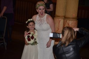A bride and flower girl mugging for the camera, while the official photographer takes their picture.