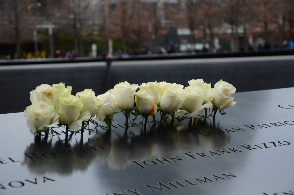 A group of white roses placed in one of the 9/11 memorial names.