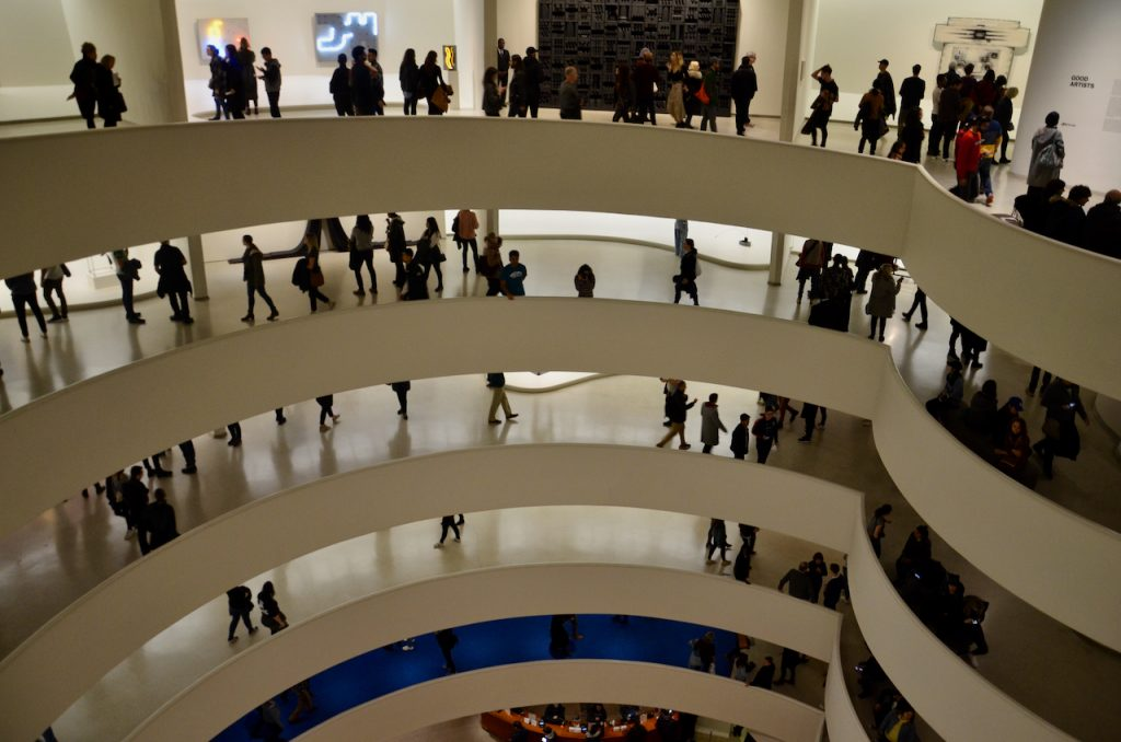 Several levels of the Guggenheim's ramped walk ways around the building all filled with people.