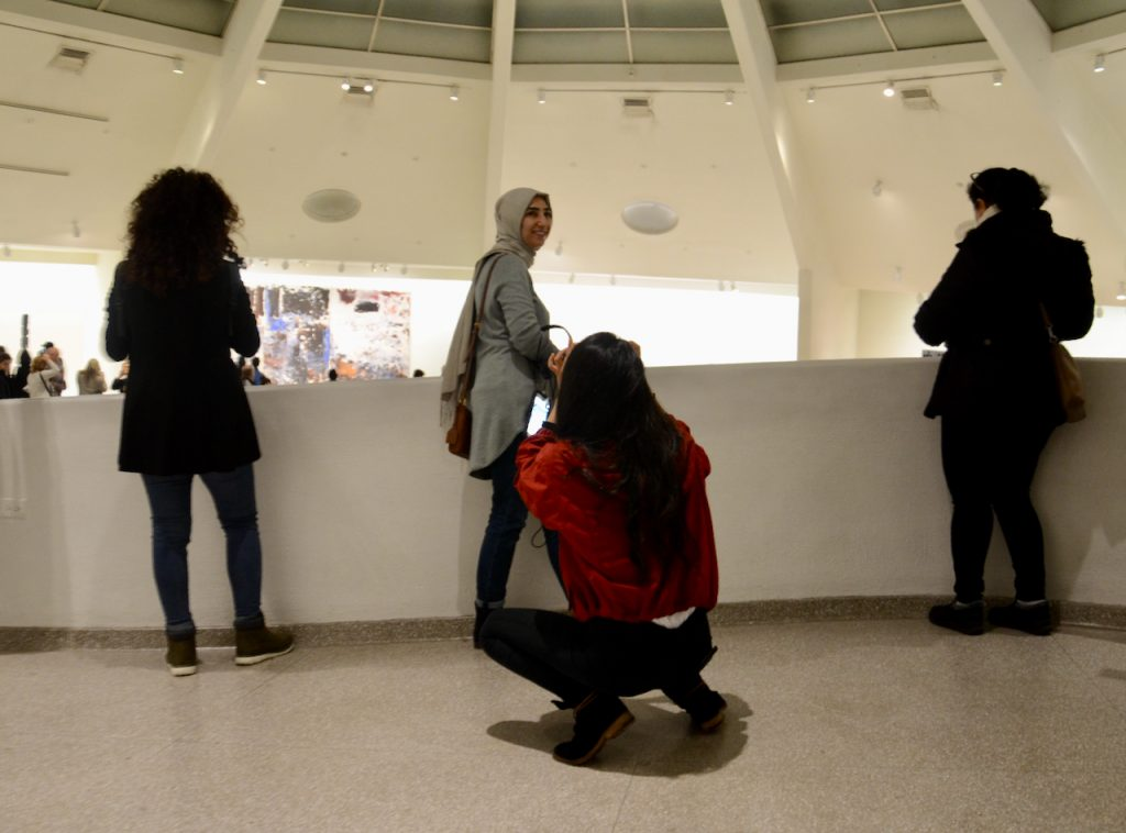 A pair of friends taking pictures at the top of the Guggenheim. A young muslim woman smiles as she poses for her friend.